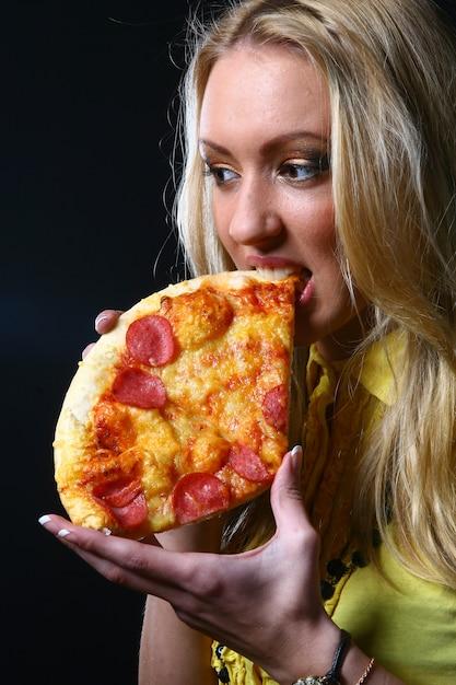 Blond meisje eet pizza Gratis Foto