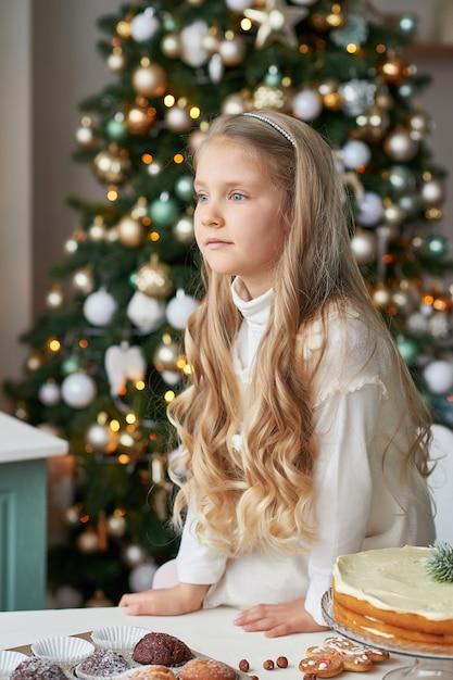Blond meisje in de keuken van het nieuwe jaar met cupcakes en snoep Premium Foto