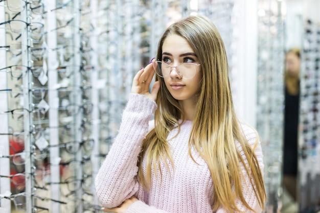 Blond meisje in witte trui kiezen nieuwe medische bril in professionele winkel Gratis Foto