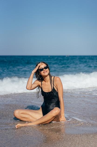 Blond meisje in zwempak dat het op zee strand looien zit Gratis Foto