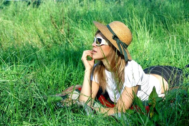Blond meisje met hoed en zonnebril die op grasgebied leggen Premium Foto