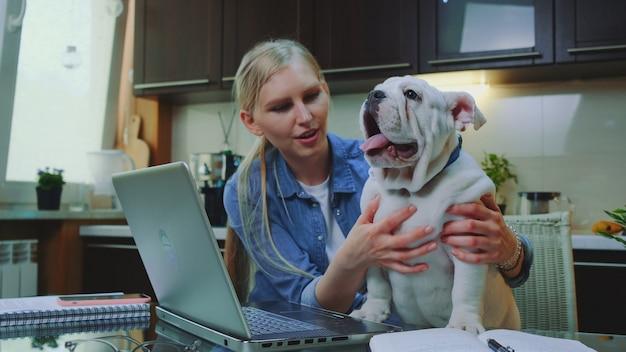 Blond meisje petting buldog en spreken met het in de keuken thuis Premium Foto