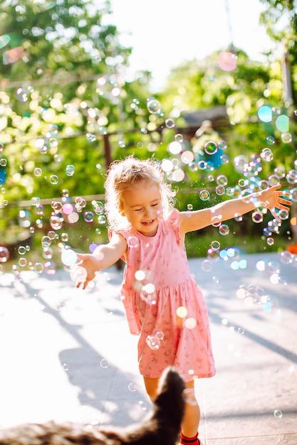 Blond meisje vangen van zeepbellen. gelukkige jeugd, zomer vakantie concept. Premium Foto