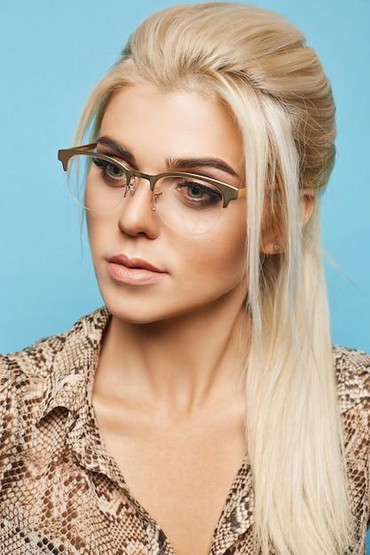 Blond model met blauwe ogen en perfecte huid in glazen op blauwe muur Premium Foto
