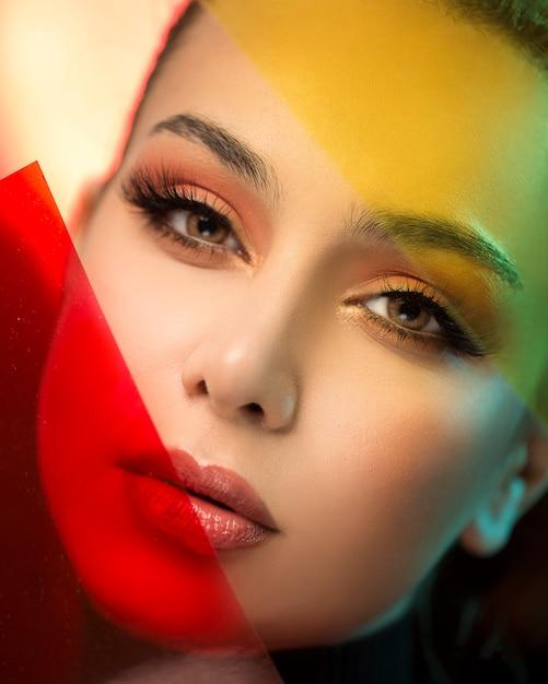 Blond vrouwelijk model dat make-up met rode en gele accenten draagt Gratis Foto