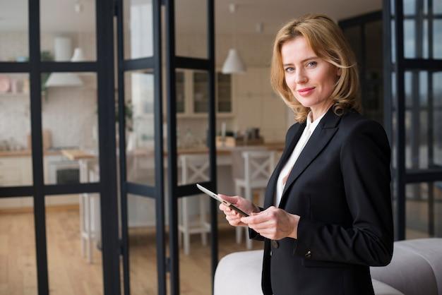 Blonde bedrijfsvrouw die tablet gebruikt Gratis Foto