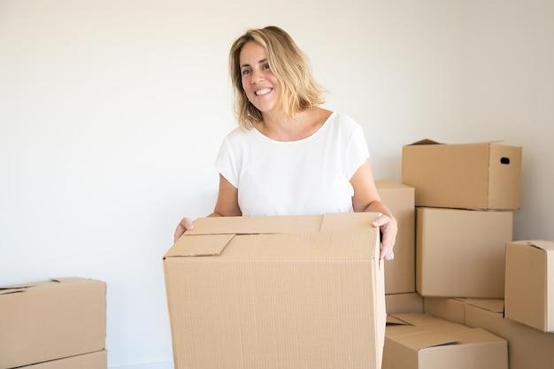 Blonde blanke vrouw met kartonnen doos in nieuw huis of appartement Gratis Foto