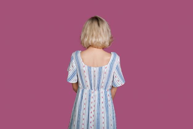 Blonde blanke vrouw op zoek naar paarse achtergrond tijdens het dragen van een jurk Premium Foto