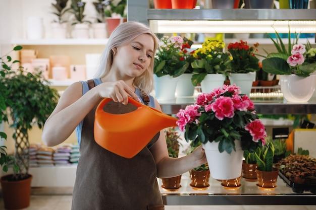 Blonde bloemist vrouw water, zorgt voor planten in de werkruimte van een bloemenwinkel Premium Foto