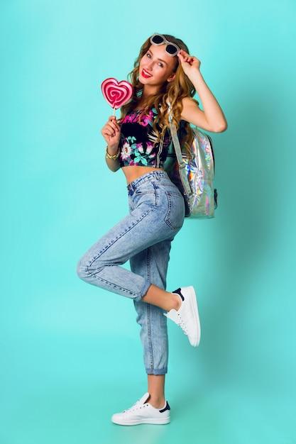 Blonde de mannequinmeisje die van de schoonheid kleurrijke roze doughnut houden. grappige vrolijke vrouw met snoep, dessert. dieet, dieet concept. junk food. felle kleuren. Gratis Foto