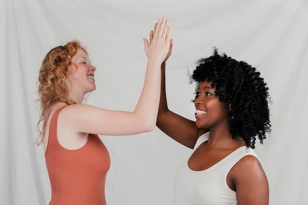 Blonde en afrikaanse jonge vrouwen die hoogte vijf geven tegen grijze achtergrond Gratis Foto
