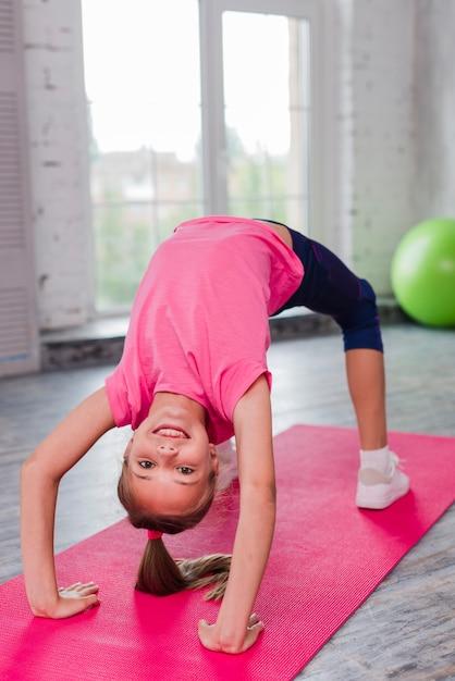 Blonde glimlachend meisje die op roze oefeningsmat uitoefenen Gratis Foto