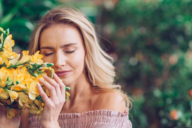 Blonde jonge vrouw die haar ogen sluit wat betreft de fresiabloemen Gratis Foto