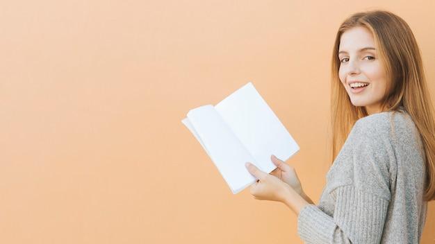 Blonde jonge vrouw die het boek van de cameraholding in hand tegen perzikachtergrond bekijken Gratis Foto