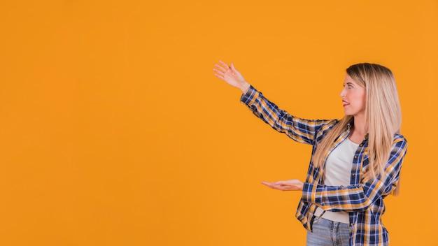 Blonde jonge vrouw die iets voorstellen tegen een oranje achtergrond Gratis Foto