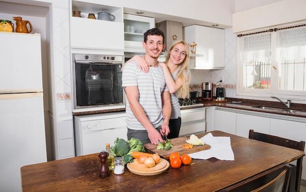 Blonde jonge vrouw die zich met haar echtgenoot scherpe groenten in de keuken bevindt Gratis Foto