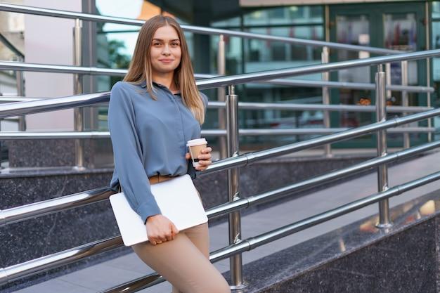 Blonde jonge vrouw lachend portret met laptop en koffie, blauwe zachte shirt dragen over modern gebouw achtergrond Gratis Foto