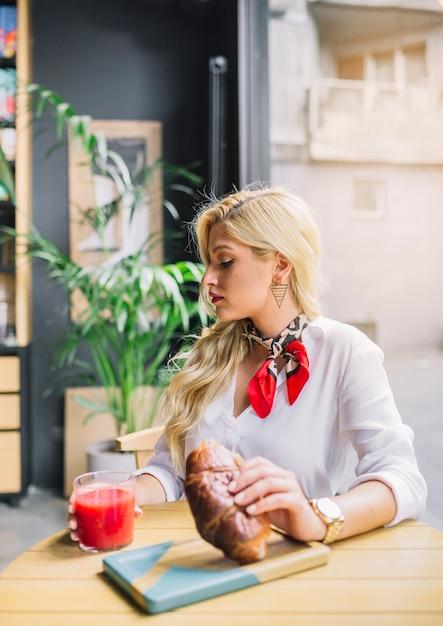 Blonde jonge vrouw zitten in de caf� holding brood en glas sap Gratis Foto
