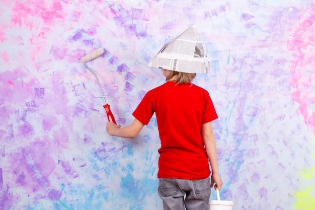 Blonde jongen achteraanzicht in rood t-shirt en grijze jeans schilderen kleurrijke muren Gratis Foto
