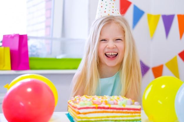 Blonde kaukasisch meisje die om camera dichtbij de cake van de verjaardagsregenboog lachen. feestelijke kleurrijke achtergrond met ballonnen Premium Foto