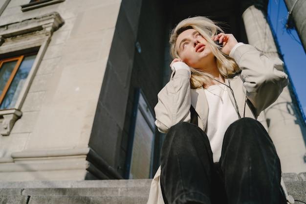 Blonde luistert muziek in een zomerstad Gratis Foto