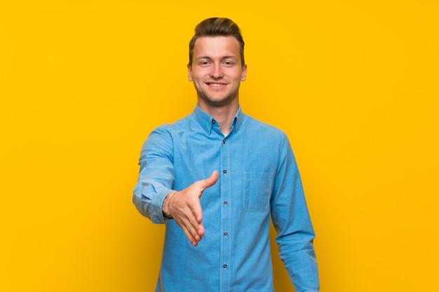 Blonde man over geïsoleerde gele muur handen schudden voor het sluiten van een goede deal Premium Foto