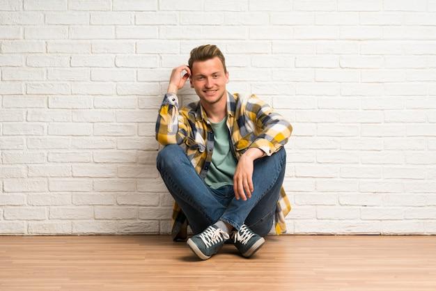 Blonde man zittend op de vloer denken een idee Premium Foto
