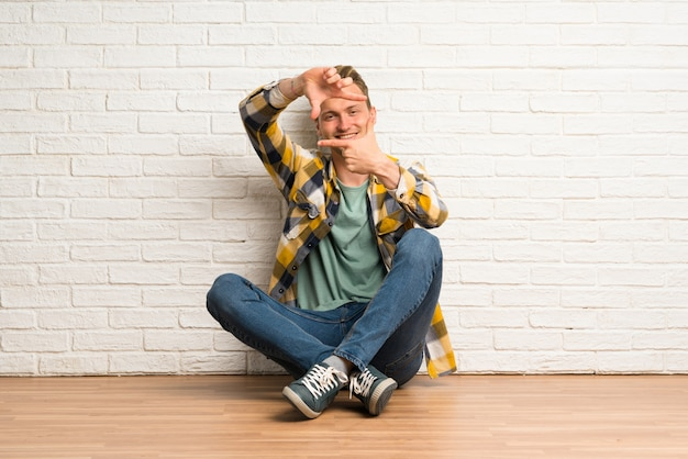 Blonde man zittend op de vloer gericht gezicht, framing symbool Premium Foto