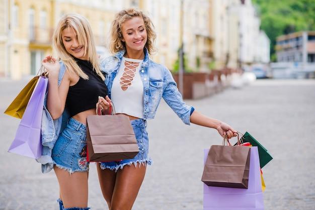 Blonde meisjes staan buiten zakken zakken lachend Gratis Foto
