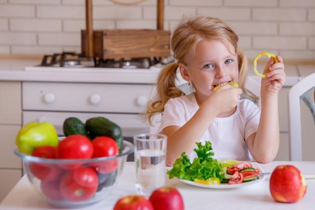 Blonde meisjeszitting bij de lijst in de keuken die groenten eten Premium Foto