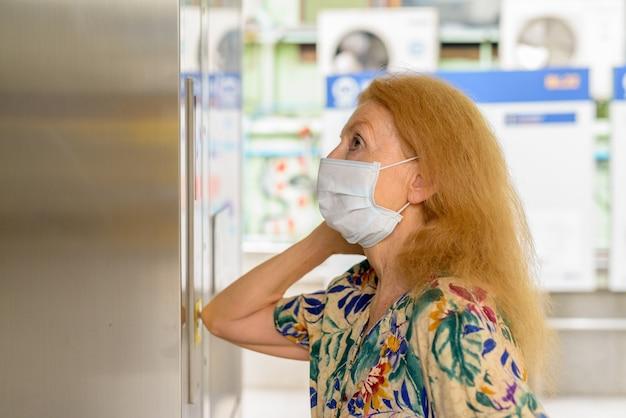 Blonde oudere vrouw die met masker op de liftknop met elleboog drukt om verspreiding van het coronavirus covid-19 te voorkomen Premium Foto