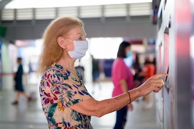 Blonde senior vrouw met masker kaartje kopen bij het sky train station Premium Foto
