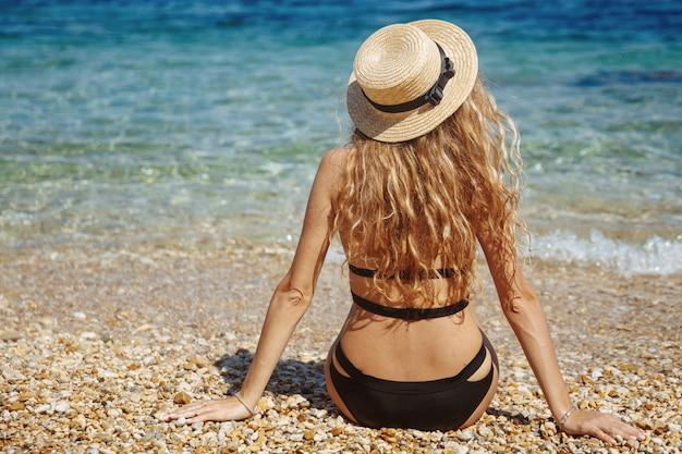 Blonde sexy meisje in zwarte bikini chillen op het strand in de buurt van de zee Premium Foto