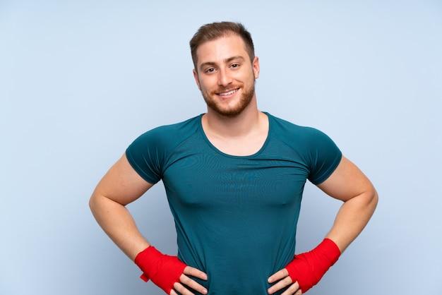 Blonde sport man over blauwe muur in boksen verbanden Premium Foto