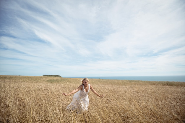 Blonde vrouw aan te raken de gewassen in veld Gratis Foto