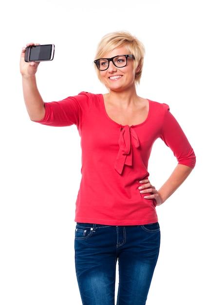 Blonde vrouw die een bril draagt die zelfportretfoto neemt Gratis Foto