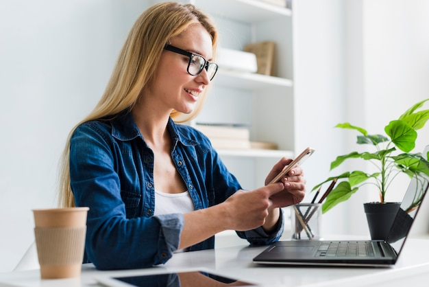 Blonde vrouw die en met smartphone werken op elkaar inwerken Gratis Foto