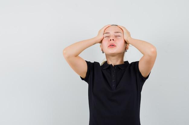 Blonde vrouw die in zwart t-shirt haar hoofd met beide handen houdt en uitgeput kijkt Gratis Foto