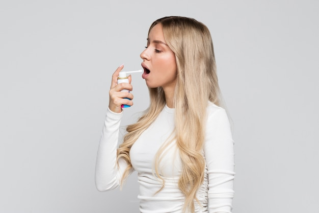 Blonde vrouw die spray gebruikt om keelpijn te behandelen. Premium Foto