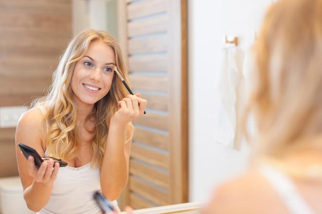 Blonde vrouw die zich voorbereidt om uit te gaan Gratis Foto