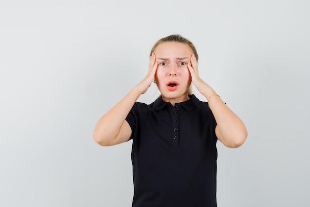 Blonde vrouw houdt haar handen op haar hoofd met open mond in zwart t-shirt en kijkt geïrriteerd Gratis Foto