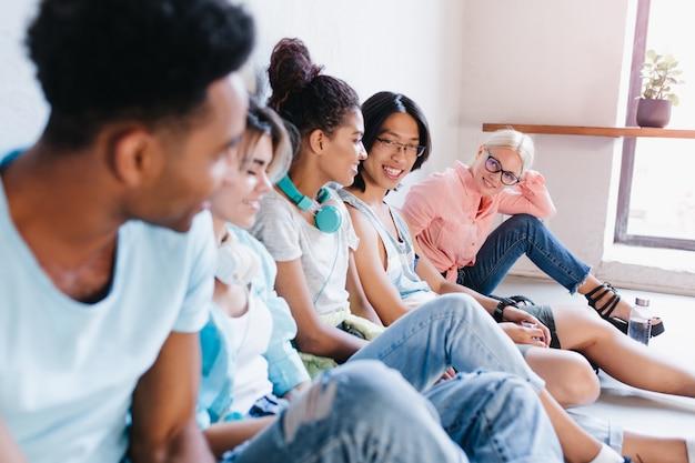 Blonde vrouw in glazen en roze shirt, zittend op de vloer en met belangstelling kijken naar haar internationale klasgenoten. portret van studenten die in campus koelen. Gratis Foto