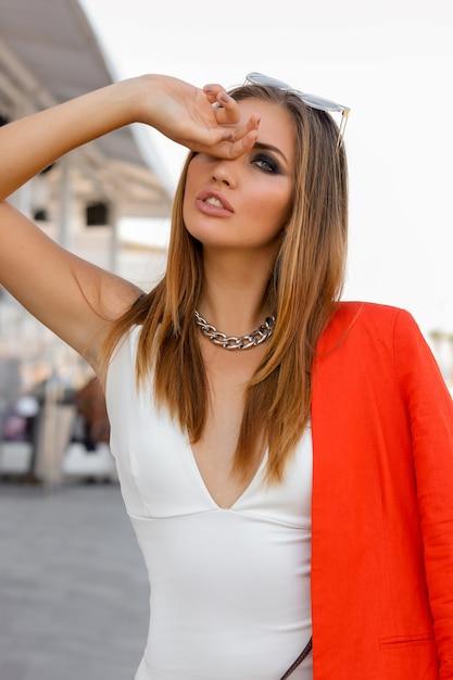 Blonde vrouw in grote zonnebril met volle lippen buiten poseren. rood jasje, stijlvolle zilveren accessoires. perfect figuur. Gratis Foto