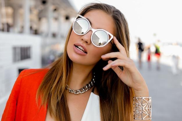 Blonde vrouw in grote zonnebril met volle lippen buiten poseren. rood jasje, stijlvolle zilveren accessoires. Gratis Foto
