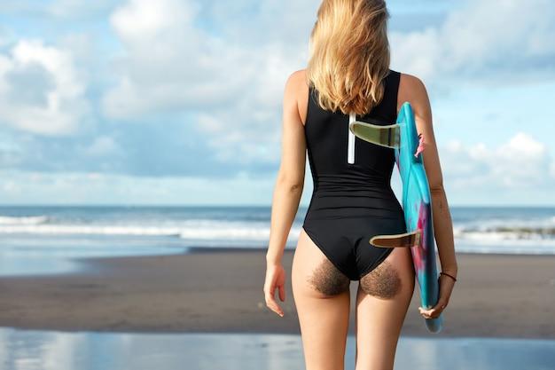 Blonde vrouw in zwembroek met surfplank op strand Gratis Foto