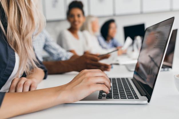Blonde vrouw met elegante kapsel tekst typen op toetsenbord in kantoor. binnenportret van internationale medewerkers met secretaresse die laptop gebruikt. Gratis Foto