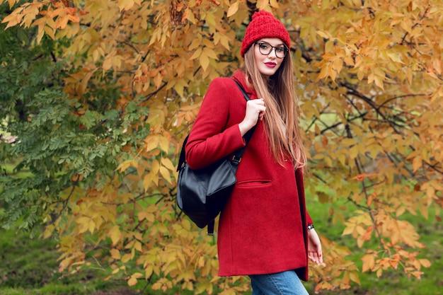 Blonde vrouw met lange haren wandelen in zonnige herfst park in trendy casual outfit. Gratis Foto