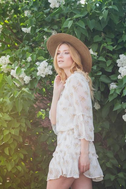 Blonde vrouw met lila bloemen in de lente Premium Foto