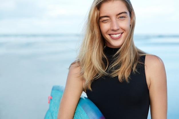 Blonde vrouw met surfplank op strand Gratis Foto