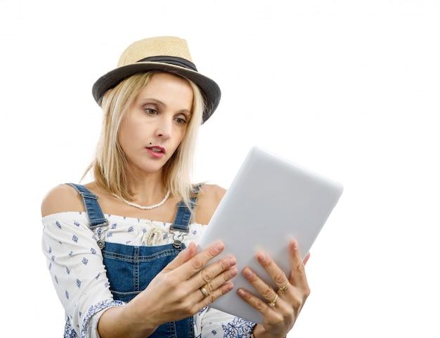 Blonde vrouw op middelbare leeftijd met tablet Premium Foto